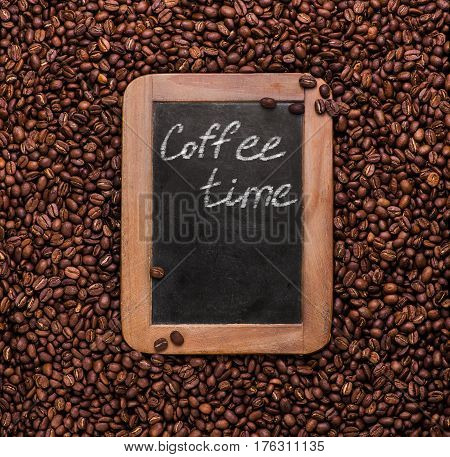 Vintage slate chalk board on coffee beans background with copy space. Texture. Roasted Arabic coffee. top view. Coffee time.