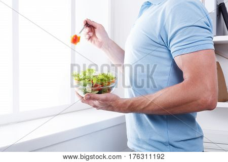Athletic man eat healthy lunch in modern interior. Unrecognizable profile male torso in blue t-shirt, hand with fork, near window with vegetable salad in bowl, diet food concept. High key image