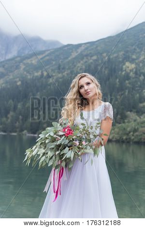 beautiful delicate girl in the air blue bride wedding dress with luxurious curls in the mountains near the lake with a wedding bouquet in hands