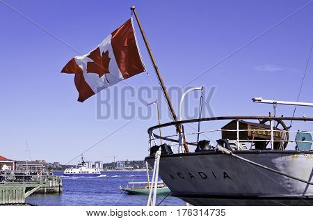 Halifax, Nova Scotia, September 23, 2015 -- Wide view of the back of a boat called the Acadia with a large Canadian flag flowing in the wind in Halifax Harbor with other boats and the ferry background on a bright sunny day in September in Halifax, Nova Sc