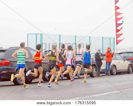 BRIGHTON GREAT BRITAIN - FEB 26 2017: Side view of group of men running in the Vitality Brighton half marathon competition. February 26 2017 in Brighton Great Britain