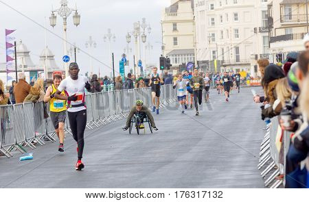 BRIGHTON GREAT BRITAIN - FEB 26 2017: Man i sports wheelchair and running competitiors in the Vitality Brighton half marathon competition. February 26 2017 in Brighton Great Britain