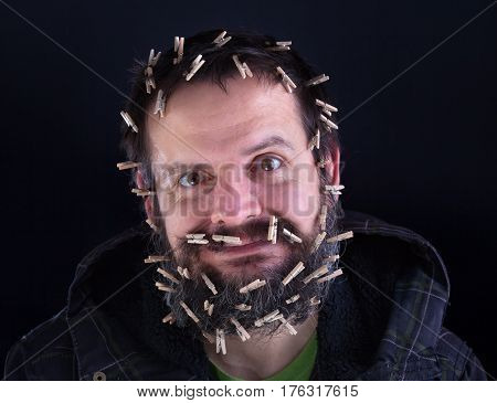 Barely holding it together - stressed man with large beard held together with lots of clothespins