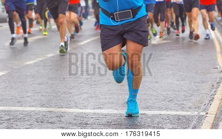 BRIGHTON GREAT BRITAIN - FEB 26 2017: Feet and legs of a running man in lead of a group of runners in the Vitality Brighton half marathon competition. February 26 2017 in Brighton Great Britain