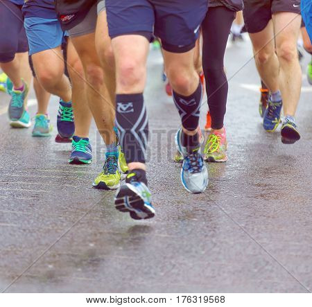 BRIGHTON GREAT BRITAIN - FEB 26 2017: Closeup of colorful running feet and legs some out of focus in the Vitality Brighton half marathon competition. February 26 2017 in Brighton Great Britain