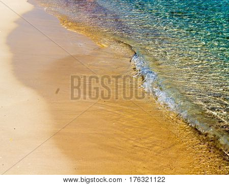 Transparent Sea Wave Gently Accumulates On The Beach Sand