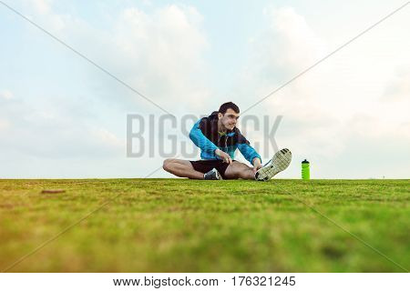 athletic sportsman with a bottle of water sitting and doing warming stretching exercise in the park