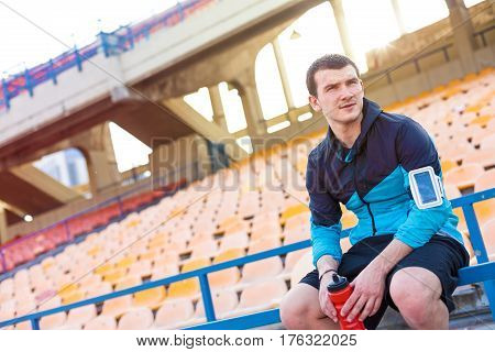 sportsman sitting with bottle of water on the railing on the stadium
