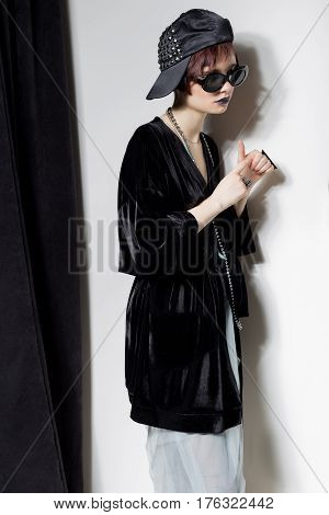 fashion shot of a beautiful young girl with a cheeky short hair in a hipster style in a black velvet jacket in Kupka Chesney and sun glasses in a studio on a black background