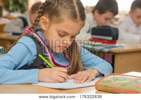 First Grader In Class Writing In Notebook