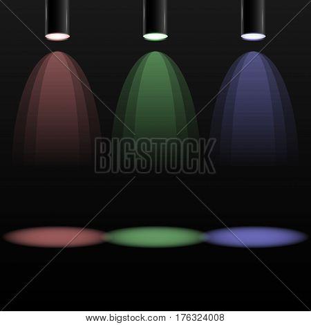 Three dark spotlights with different color lights