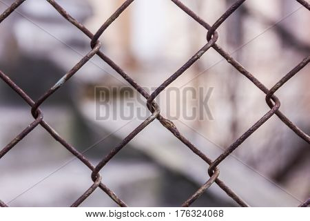 Rusty Steel Chain Link Or Wire Mesh As Boundary Wall. There Is Still Concrete Block Wall Behind The