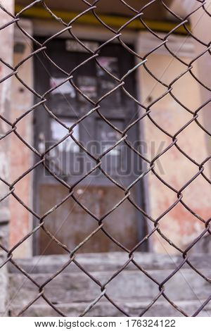 Steel Chain Link Or Wire Mesh As Boundary Wall. There Is Door Behind The Mesh.