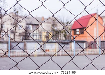 Rusty Steel Chain Link Or Wire Mesh As Boundary Wall. There Is Yard To The House With A Red Roof Beh