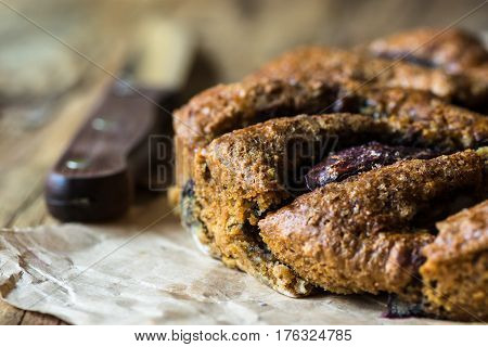 Vegan eggless whole wheat plum cake on parchment paper knife wood kitchen table close up rustic kinfolk style
