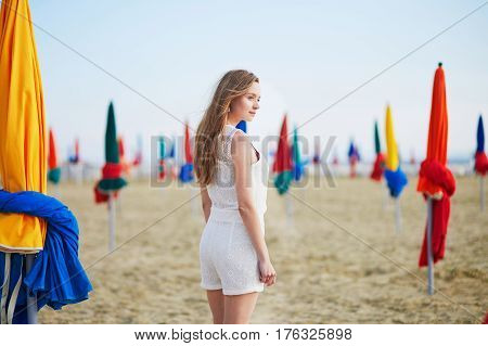 Woman With Famous Colorful Parasols On Deauville Beach In France