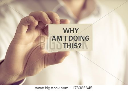 Businessman Holding Why Am I Doing This ? Message Card