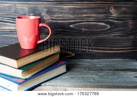 Hot coffee or tea, cocoa, chocolate cup on book with copy space for text against the wooden background