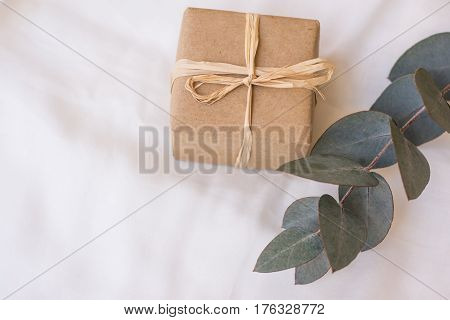Gift box wrapped in craft paper tied with twine branch of silver dollar eucalyptus on white linen fabric present concept romantic