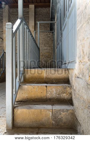 Stone staircase leading to a narrow passage framed by blue wooden doors and balustrade leading to stone wall at historical traditional bathhouse (Hamam Inal) Cairo Egypt