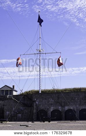 Halifax, Nova Scotia, September 23, 2015 -- View of a large flagpole and mast with three flags blowing in the wind on the fortress walls of the citadel in Halifax, Nova Scotia sunny day in September