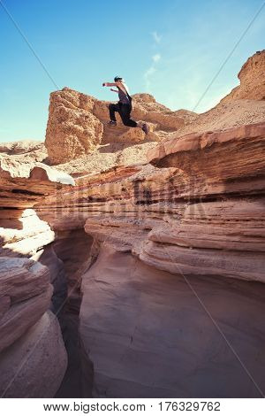 brave man jumping over the cliff in canyon, and little motion blur