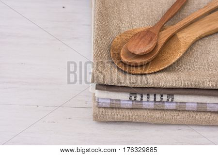 Stack of linen cotton kitchen towels handmade wooden spoons on white kitchen table Provence style interior design coceptual