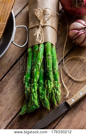 Bunch of fresh asparagus tied with twine garlic knife kitchenware on wood table top view cooking concept