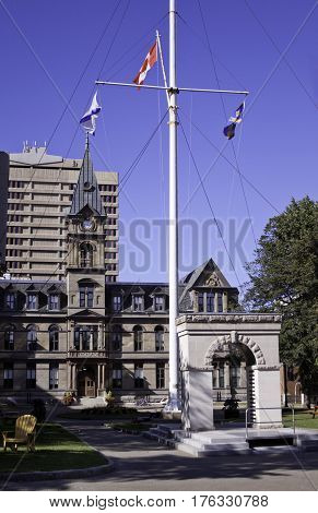 Halifax, Nova Scotia, September 23, 2015 -- View of the Halifax City Hall in downtown Halifax, Nova Scotia with a memorial to the fallen soldier in the forefront with flags blowing in the wind on a bright sunny day in September