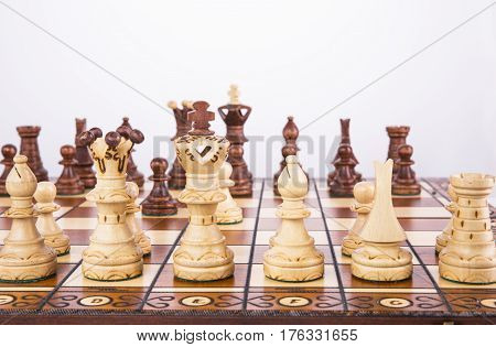 Close up of wooden chess pieces on a chessboard with copy space above