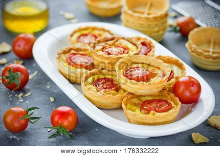 Cheese tomato tartlets puff pastry appetizers mini-pizzas with cheese and cherry tomatoes