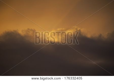 Majestic sunset golden sky hidden by brown waves of clouds horizontal oriented photo