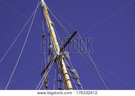 Wide view looking up at a wooden mast with rope rigging on a beautiful sunny bright day in September in Halifax Nova Scotia