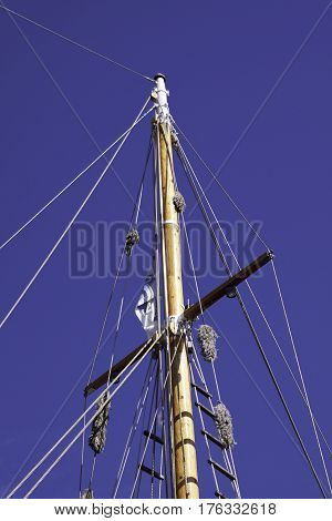 Vertical view looking up at a wooden mast with rope rigging on a beautiful sunny bright day in September in Halifax, Nova Scotia
