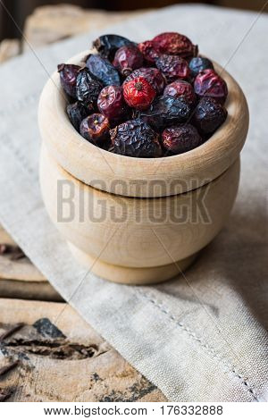 Dried rose hip berries in wood bowl on linen towel health concept natural medicine closeup soft colors