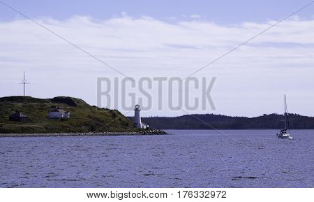 Wide view of the single lighthouse on Georges Island National Historic Site with a sailboat in the Halifax Harbor on a bright sunny day in September in Halifax, Nova Scotia