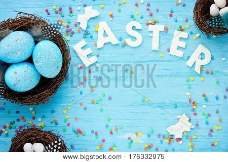 Easter background with blue and white eggs in nest butterfly and sugar sprinkles on a blue table top view with copy space Happy Easter concept
