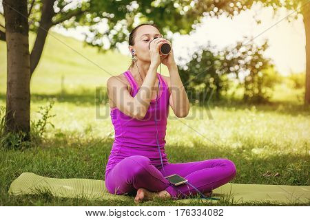 athletic girl drinking smoothie. Athletic girl holding a strawberry smoothie. Girl is engaged in yoga on the nature and drinking smoothies