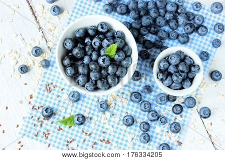Freshly picked blueberries in white bowl. Juicy and fresh blueberries. Bilberry on wooden background. Blueberry antioxidant. Concept for healthy eating and nutrition
