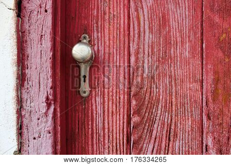 Closeup of old red-stained, very grainy wooden door and silver doorknob with keyhole