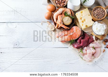 Assortment of healthy protein source and body building food. Meat beef salmon chicken eggs dairy products milk cheese yogurt beans quinoa nuts oat meal. Copy space background, top view flat lay