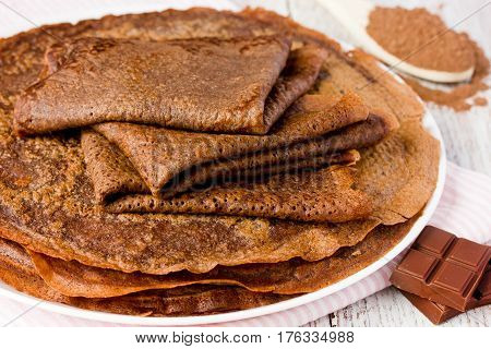 Thin chocolate pancakes from yeast dough with cocoa powder. Shrove Tuesday. Selective focus