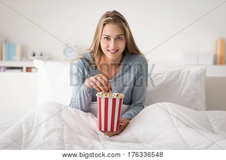 Happy woman relaxing in bed and watching movies on tv she is eating popcorn