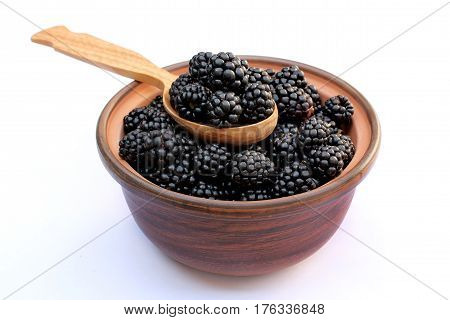 Juicy ripe blackberries in a bowl with a spoon isolated on white