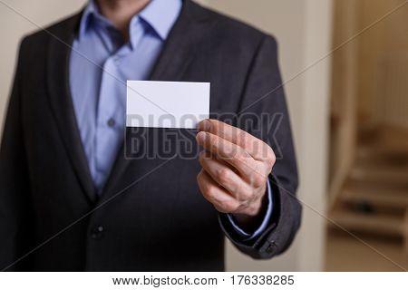 Businessman holding visit card. Man showing blank business card. Person in black suit. Mock up design.