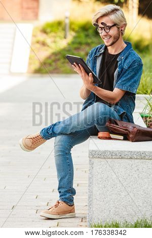 Hipster Smiling Guy With Tablet Sitting On Ledge