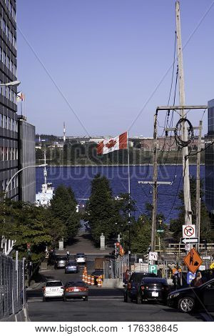 Halifax, Nova Scotia, September 23, 2015 -- Looking down at Halifax Harbor, Nova Scotia from the citadel we see a large Canadian flag flying by the harbor lots of traffic and people milling about on a bright sunny day in September