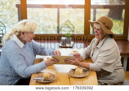Senior women holding tablet. Cake and coffee on table. New os is much better.