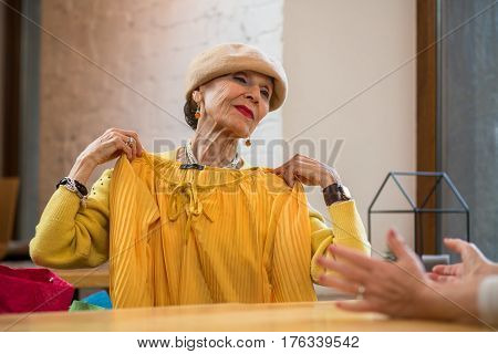 Senior woman is holding clothes. Stylish old lady. Light colors suit me.