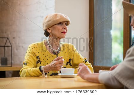 Senior woman and coffee cup. Elderly lady with suspicious face. Tell me more.